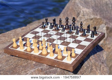 Chess Board With Chess Pieces On Rock With River Embankment Background