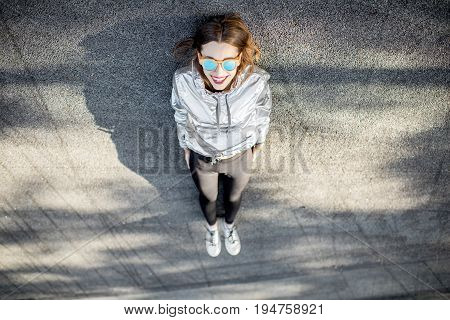 Lifestyle portrait of a modern woman in silver jacket and shoes lying outdoors on the asphalt road