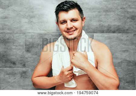Handsome young man staying in bathroom with white towel on shoulders. Brunette muscle guy with shirtless torso holding towel and smile. Getting ready to go out. Wellness skincare concept.