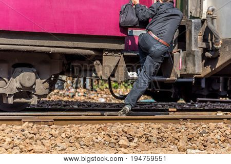 People step up to railway train on the railroad tracks in Bangkok station. Many people in Thailand popular travel by train because it is cheaper.