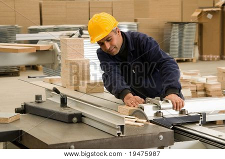 Carpenter cutting wood on electric saw, focus is on the blade of the tool - a series of INDUSTRIAL IMAGES.