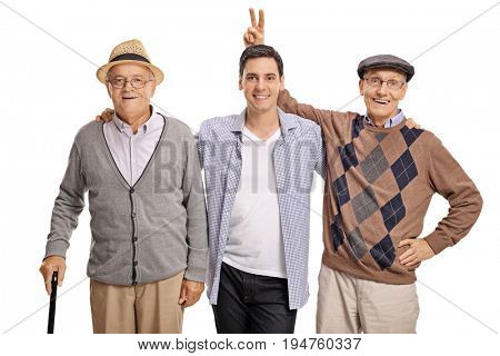 Young guy with two mature men with one of them pranking him with bunny ears isolated on white background