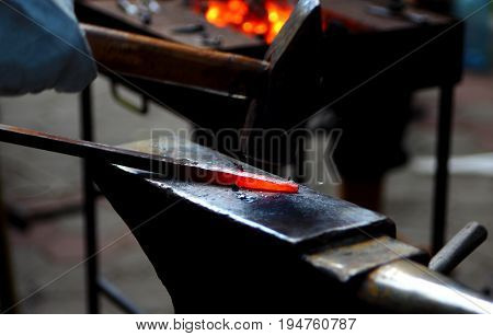 Blacksmith working metal with hammer on the anvil