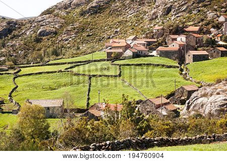 Stone village with pastures, Picturesque Portuguese mountains with village, Portuguese fertile field in summer, Pasture for cattle with house, Portuguese mountains