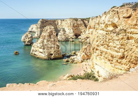 Bay with boat and tourists at Praia da Marinha, Beautiful Portuguese coast to swim, Bay in Portugal Algarve
