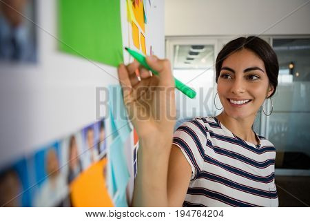 Smiling young woman writing on sticky note in creative office