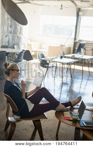 Side view of businesswoman reading book while relaxing on chair at office