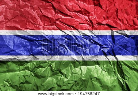 Gambia flag painted on crumpled paper background