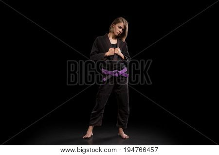 Inflated girl in black kimono posing on black background