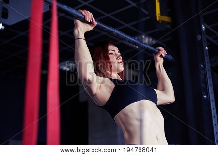Close-up of sexy fitness girl pulls up in the gym. Fitness woman in black sport top with perfect fitness body in gym performing abdominal exercises on the horizontal bar