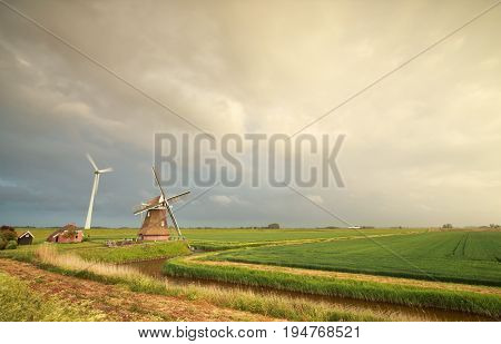 new and old windmill over rainy sky Holland