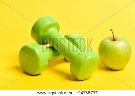 Green Lightweight Dumbbells And Greenish Yellow Apple Fruit