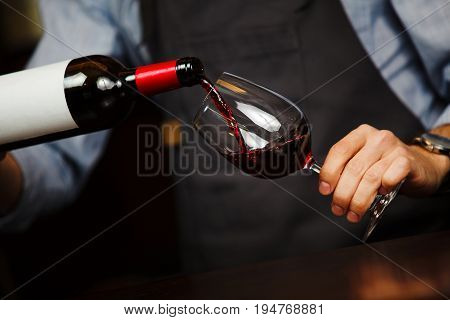 Man pouring wine into wineglass, male hand holding bottle of red expensive alcoholic beverage, closeup photo
