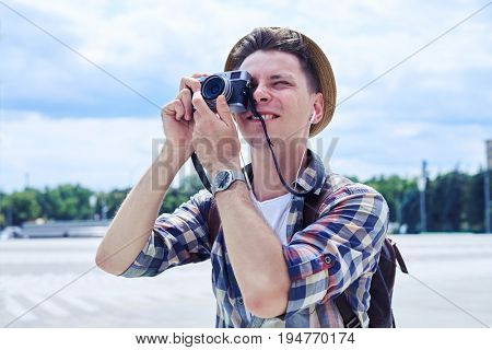 Close-up shot of traveler hipster young man takes photographs with vintage photo camera