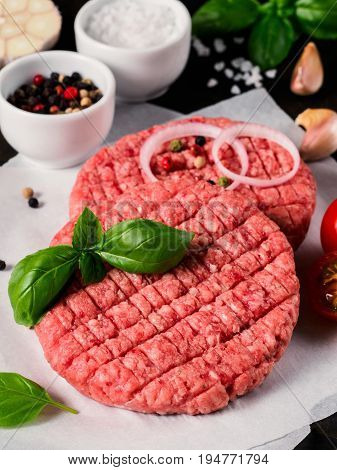 Close up view of two raw meat steak cutlets for burger with vegetables, spices and fresh basil. Making homemade burger. Vertical.