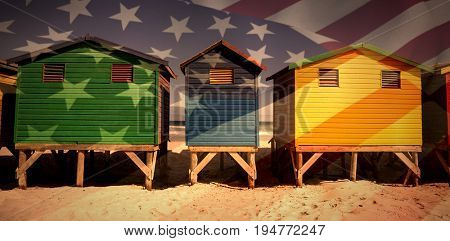 Close up of the us flag against colorful huts on sand at beach