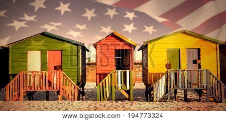 Close up of the us flag against multi colored huts on sand against clear sky