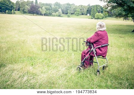 senior walking with walking frame in park