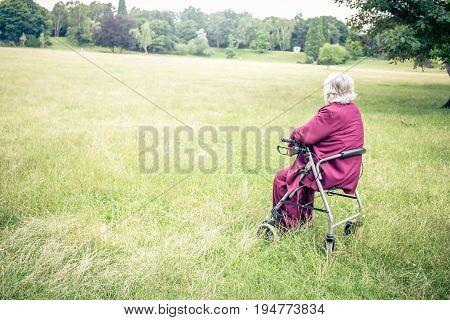 senior walking with walking frame in park