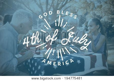 Digitally generated image of happy 4th of july message against happy family having a picnic