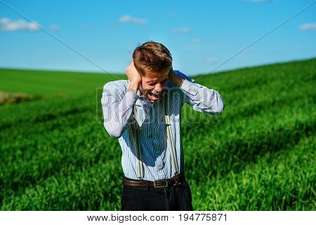 Handsome Man In The Field Is Closing His Ears With His Hands:trying To Ignore, Not To Hear Something