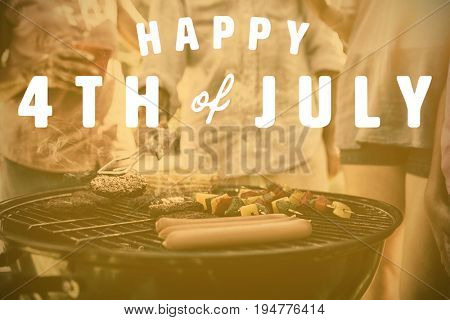 Digitally generated image of happy 4th of july text against family having a barbecue
