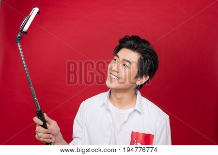Happy young asian man taking self portrait photography through smart phone over red background.
