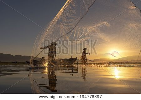 Asian fisherman on wooden boat casting a net for catching freshwater fish in nature river in the early morning before sunrise .Silhouette of traditional fishermen throwing net fishing at sunrise time.
