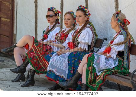 ROMANIA TIMISOARA - JULY 9 2017: Mature women dancers from Poland in traditional costume relaxes at the international folk festival