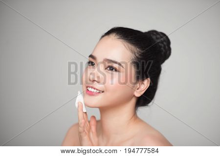 Happy smiling beautiful asian woman using cotton pad cleaning skin.