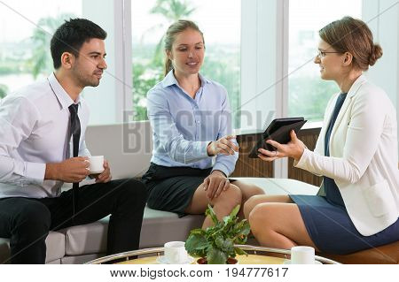 Smiling young business woman showing something on tablet computer screen to male and female colleagues. They are drinking coffee and sitting on sofa and armchair at table in office lounge.