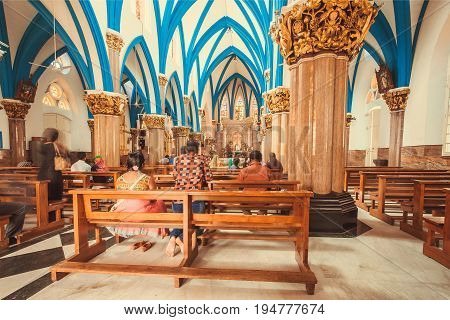 BANGALORE, INDIA - FEB 14, 2017: Church interior with praying women and men under dome of the 17th century catholic St. Mary's Basilica on February 14, 2017. Bangalore is the third most populous indian city