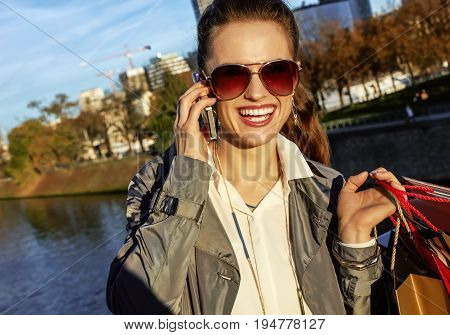 Get your bags ready for the Paris autumn sales. smiling young elegant woman in trench coat with shopping bags talking on a cell phone near Eiffel tower