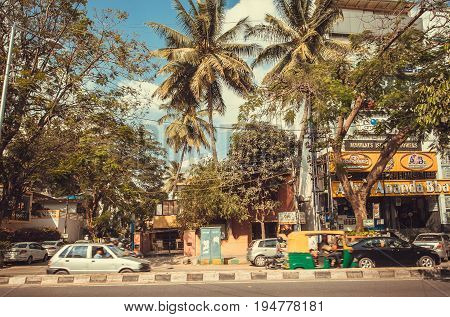 BANGALORE, INDIA - FEB 14, 2017: Tropical street with palm trees and autos on busy road on February 14, 2017. With population 8.52 million Bangalore is the third most populous indian city