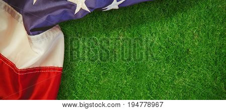 Creased US flag against closed up view of grass