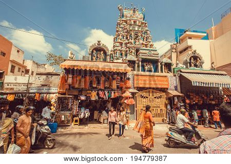 BANGALORE, INDIA - FEB 14, 2014: Many people walking on street with market and Hindu temple on February 14, 2017. With popul. 8.52 million Bangalore is third most populous indian city