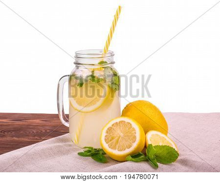 A glass jar with a yellow straw and a cooling mojito with bright green mint leaves and a yellow lemon on a brown table, isolated on a white background. Tasty fresh cocktail with ripe and bright yellow lemon and green mint.