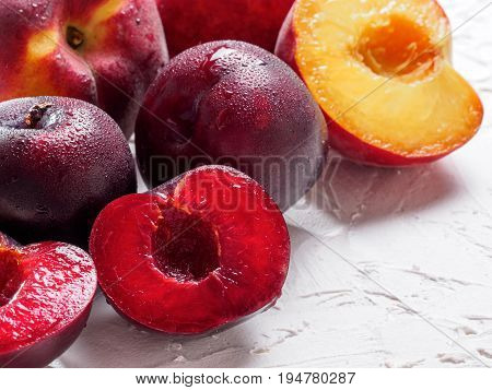 Close up view of fresh plum and peach on white concrete background. Copy space.