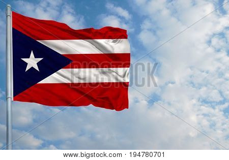 National flag of Puerto Rico on a flagpole in front of blue sky.