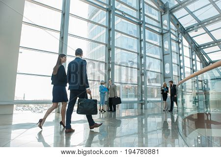 Business people walking in modern glass office building