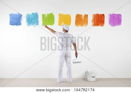 Rear view of painter man pointing with finger the colors on wall with paint roller and bucket isolated on white