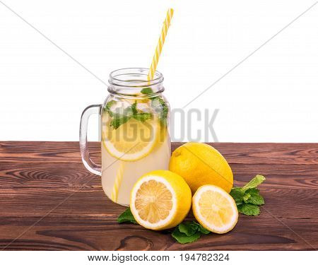 A jug full of refreshing and cold beverage with fresh and ripe lemon, crushed ice and green mint and a yellow straw. Refreshing and tasty mojito or lemonade with fruits isolated on a white background.