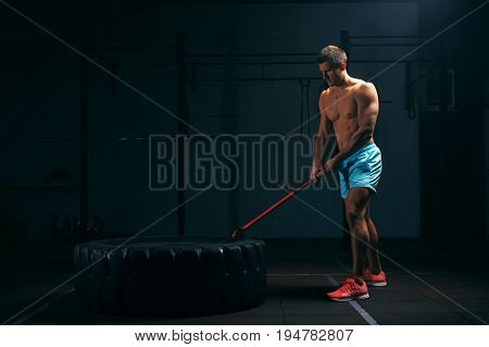 Muscular man working out with huge tire and hummer at the gym. Weightlifting or functional training. Sports and fitness concept.