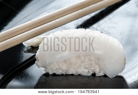 Japanese sushi made of rice and sea bass with chopsticks on a black plate. The horizontal frame.