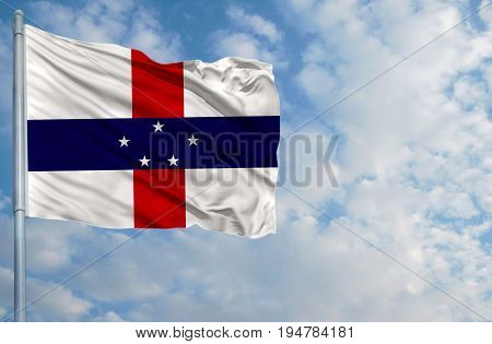 National flag of Netherlands Antilles on a flagpole in front of blue sky.