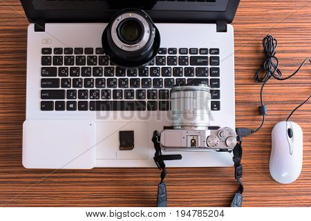Camera Photographer workplace , Camera, Laptop ,calculations ,  on wooden desk. concept of photographer work station.