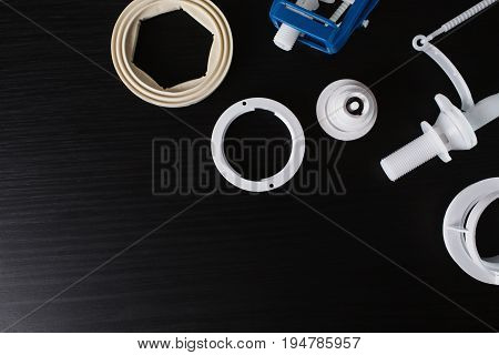 Details for toilet tank on the table. Drain mechanism and release button from the toilet tank. Equipment for toilet. Toilet bowl