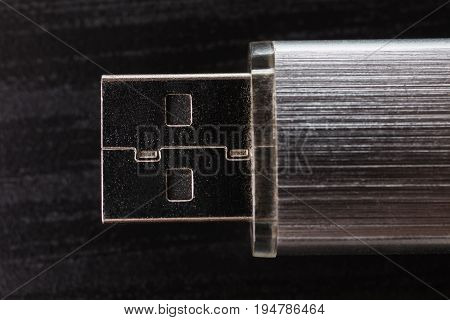 Silvery usb flash drive on a black table close-up. A metal usb flash drive for storing memory on a dark background with hard light.  Cable for connecting with usb flash drive. Gray usb flash drive on the table. Connection with a usb flash drive. Move file
