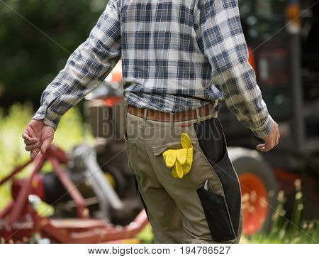 Close up of gardener pocket with sticking protective glover Tractor with mower in background in public park