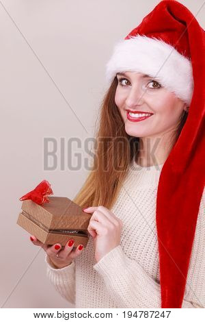 Cheerful woman wearing santa claus hat opening golden gift box with red bow. Christmas time giving and happiness concept.